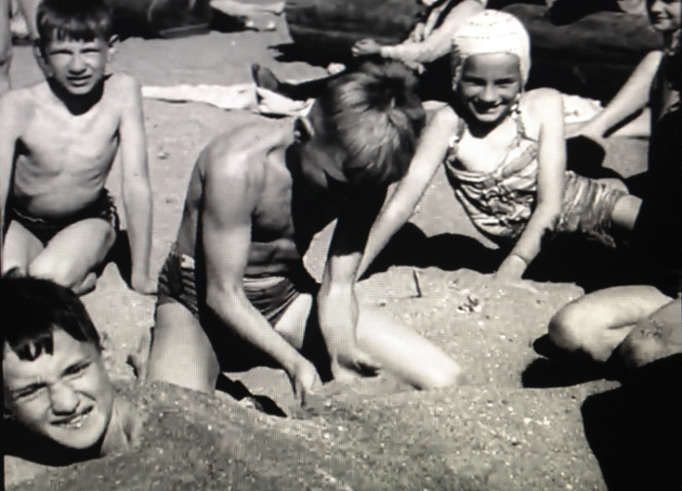 "Screen shot of children playing on a beach in Vancouver from ""Gateway to Asia"", NFB, 1945."