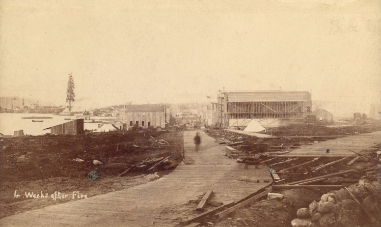 4 Weeks after Fire. Photograph shows a view looking east from Richards Street toward the intersection of Water Street and Cordova Street, plank roads, buildings including the Greyhound Hotel under construction and Princess Louise Tree. Photo: J.A. Brock and Company, City of Vancouver Archives, AM54-S4-: Str P129.