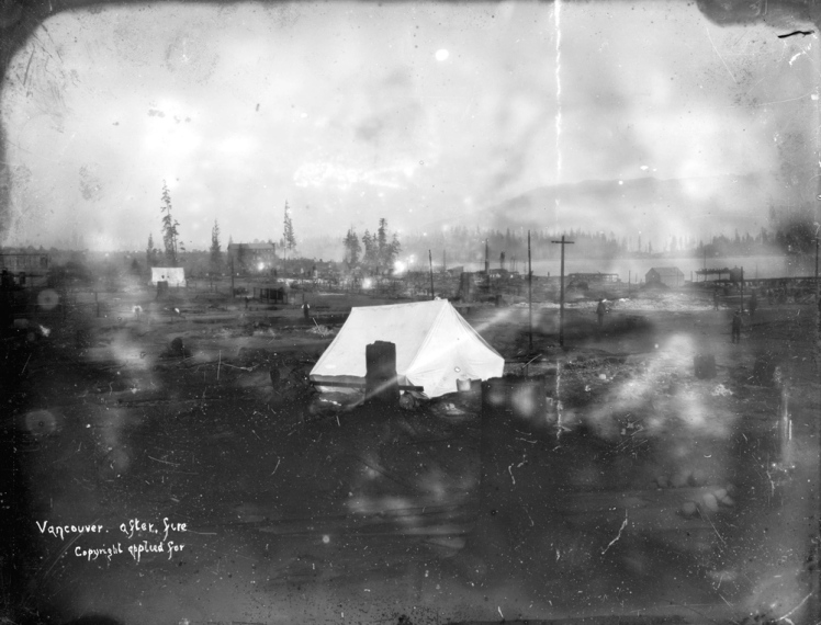 Vancouver after fire. Photograph shows George R. Gordon's tent among debris at Cordova Street and Carrall Street and the Regina Hotel in the background. Photo: Vintage print attributes photograph to J.A. Brock and Co. Photographers, H.T. Devine was likely the photographer. City of Vancouver Archives AM54-S4-: LGN 455