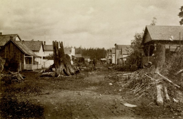 """1885 view of street in Granville, now Vancouver, BC. Copy of photograph titled """"Main Street, Granville.'  [Looking East on Water Street near Carrall] From """"Wanderings with a Camera"""" by Erskine Beveridge. Photo:  Erskine Beveridge, RCAHMS, DP042683"""
