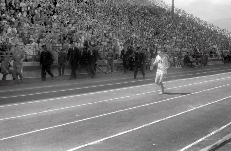 Jim Peters entering Empire Stadium, he stumbles around the track before completely collapsing, August 7th, 1954. Photo: Alvin Armstrong, CBC Still Photo Collection