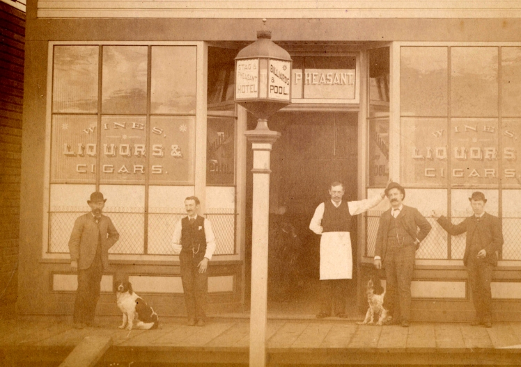 George Cary with dog (far left) poses in front of the Stag nad Pheasant Hotel. Photo: CoV Archives - Hot P22.1